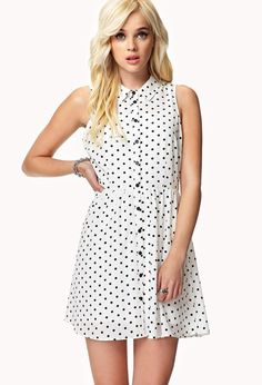 A sleeveless polka dot shirt dress featuring a basic collar. Full button placket. Darted bust. Sh...