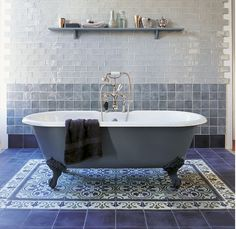 A beautiful - and practical - way of adding a 'rug' to the bathroom floor is to use feature encaustic tiles.