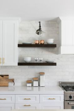 kitchen cabinets adorning brass hardware, two stacked dark stained floating shelves are lit by a clear glass swing arm sconce mounted on carrera marble backsplash tiles pointing down towards cabinets topped with white quartz countertops fixed beside a stainless steel oven range placed under a while paneled hood.