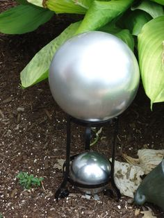 DIY gazing balls for under 7 bucks = Old bowling balls painted with metallic paint and a repurposed plant stand to display them!