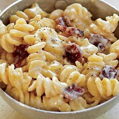 Bacon Mac and Cheese:    Ingredients    1teaspoon kosher salt, plus more for salting the pasta water     2 cups firmly packed shredded sharp Cheddar cheese         1pound fusilli (corkscrew)     ¼ teaspoon freshly ground black pepper     ¾ pound bacon, diced about 1 cup cooked     ½ cup sour cream, for garnish    3 cups heavy cream     ½ cup thinly sliced scallions, (white and green parts), for garnish