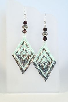 Handmade diamond shaped beaded earrings. A minimalist design that is flexible for any occasion. These lightweight earrings are made with steel finished hex cut beads in defining but mesmerizing lines which are eye-catching against beautiful pearl Sea Foam Green seed beads with Jasper Stone rounds and antique plated spacers. These earrings bring out a Boho Hippie vibe that I love. The Earwire is 99.9% pure Silver Plated and nickel free. Just over 3 inches from top of the ear wire to the…