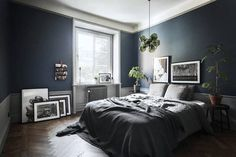 Delightful dark blue walls in the bedroom of a Stockholm space. Bosthlm.