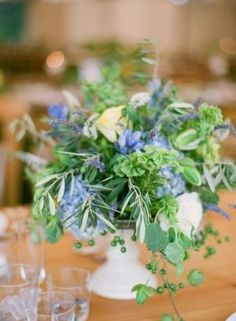 Half the tables will have a grapewood branch inside a white compote vase filled with light blue hydrangea, blue cornflowers, blue thistle, navy privet berries, red ranunculus, seeded eucalyptus, variegated pittosporum, and herbs. Surrounded by clear votive candles.