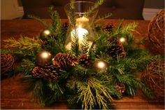 Christmas Centerpiece - This Christmas centerpiece was created using small pine branches, pinecones, gold Christmas bulbs, a hurricane candle holder and white candle. Beautiful.