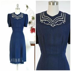 Vintage late 1930s dress is absolute perfection in navy blue rayon crepe. It embodies a late 30s silhouette, with lightly padded puffed sleeve shoulders and a swishy skirt, shaped with four long crisp darts that open to pleats. The dress has a high neckline with fantastic sheer collar and appliqued cutwork. Its flirty, fresh and quintessential. It closes on the side with a sturdy metal zipper and a hook at the back of the neck. The temptation to keep this is very, very strong…
