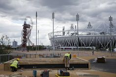 Construction crews work outside the Olympic Stadium as preparations continue for the 2012 Summer Olympics, Sunday, July 15, 2012, in London. At left is the Orbit.  (AP Photo/Jae Hong) Photo: Jae Hong, Associated Press / SF