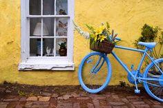 Blue bike against yellow wall