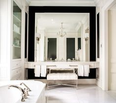 Elegant master bathroom features a full wall clad in a framed mirror lined with a white floating washstand fitted with his and hers sinks and towel bars alongside a white cowhide bench tucked below.