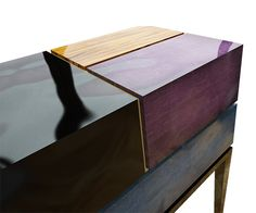 The Proportion II Nightstand combines an eccentric and luxury mix of black lacquer over silver leaf, radiant orchid lacquer over gold leaf, petrol blue lacquer and caviuna wood.