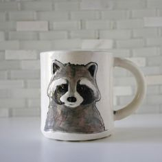 Best known as nocturnal bandits, this handmade raccoon mug will steal your heart. details: This mug is crafted in a durable stoneware clay body. The bottom has a knobby foot and is stamped with my brand Hadley Clay. Glazed on the inside with a high gloss yellow glaze and on the outside with multiple high gloss glazes. The colors will never fade. Food safe, non-toxic. Microwave and dishwasher safe. Standard mug size - 4 tall, holds 14 ounces. Includes gift box and artist card. Order gift…