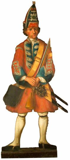 """Dummy Board of a Grenadier of the Royal Scots Regiment,"" 1738 - Life-size, cut-out figures painted on wood, often called dummy boards, were fashionable in grand houses in the eighteenth century. They were a sort of decorative joke designed to surprise visitors. Standing at the end of a passage or in the corner of a room, a dummy board would look, at first sight, like a real person."
