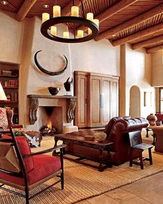 Designer Patty Burdick helped homeowners Mary Beth and Gates Hawn develop an authentic Southwest look ... The great-room's soaring 20-foot-high ceilings are constructed with latillas — peeled pine tree limbs supported by massive vigas (shown). A tufted leather chaise offers a comfy space to lounge in front of the fire. A braided sisal rug, an iron chandelier, and mounted horns above the mantel add an organic touch to the space.