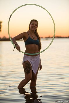 Water Hooping with Sofia Fletcher. Sofia spins up a beautiful  isolation in the water while hooping at sunset at Symbiosis. Photo by Kenny Hoff.