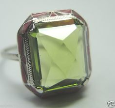 ANTIQUE ART DECO PERIDOT ENGAGEMENT RING RE-564  {International Buyers Are Responsible For Customs & Duty Fee's}  CIRCA ~ 1920'S  EMERALD SHAPE ~ PERIDOT (No Scratches, Chips, Nicks, etc)  ROSE CUT  MEASUREMENTS ~ 11.61 MM (0.457 INCHES) x 9.31 MM (0.3665 INCHES)  APPROXIMATELY ~ 4 CARAT + OR -  COLOR ~ LIME GREEN  METAL ~ 14K WHITE SOLID GOLD  WEIGHT ~ 2.9 GRAMS  ENAMEL ~ SHADES OF PINK SIZE ~ 7 (SIZABLE) U.S.A. & CANADA (Inquire About Sizing Cost)