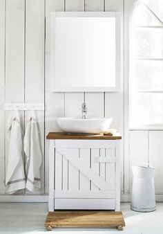The white panels and simple, wooden sink make this bathroom simple, rustic and chic.