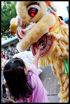 A litte girl offers a dollar to the lion during the Lion Dance at the Chinese New Year Parade in Chinatown.     We need more money! Check out:   http://www.reallyfastmakemoney.com