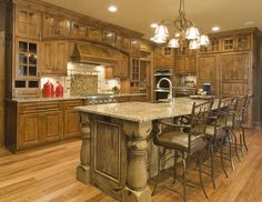 arched hood, flanking cabinets, cabinets, cabinetry, kitchen, distressed, glazed, taupe, tank, crown modling, furniture feet, panelized ends, columns, custom, traditional, island, sink in island, hood