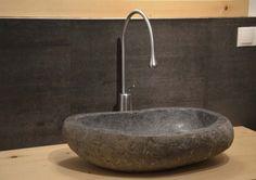 ein Fluss-Steinwaschtisch kombiniert mit einer Goccia Armatur in chrom gebürstet, eingebaut in einem Badezimmer in Freienfeld