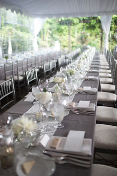 Family style reception with white chiavari chairs, gray table linens ...