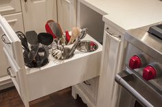 Cool way to organize your utensils.  Looks like to the right is a pull out spice rack.  I personally would switch the two only because you shouldn't store your spices near heat..