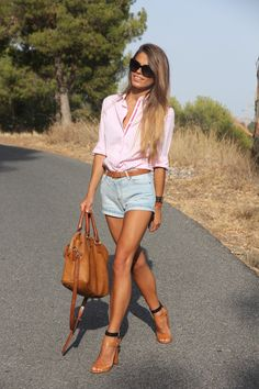 Button down blouse tucked into denim high waist mini shorts with matching heels and handbag.