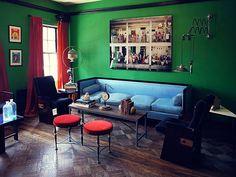 Sala clássica com paredes verdes, sofá azul de veludo, baquetas e cortinas vermelhas e piso de madeira