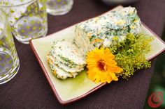 Burro aromatizzato alle erbe: prendiamo il burro a temperatura ambiente e tritiamo un mazzetto di erbe aromatiche (timo, prezzemolo, basilico), un pizzico di sale e uno spicchio d'aglio schiacciato. Aggiungiamo un po' di petali di calendula, per dare una nota di colore. Impastiamo il tutto, formiamo un panetto e lo rimettiamo in frigo per farlo rassodare. Prima di metterlo in tavola, lo ripassiamo nel trito di aromi.