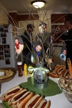 """One Year Old birthday party--branches in a vase and photos cut out from each month to make the """"leaves"""""""