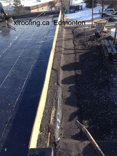 In this picture you can see the embedded gravel from the existing roof has been scraped off by the Edmonton roofing contractor. This has to be done in order to tie in the new SBS membrane to the tar and gravel membranes.