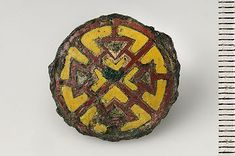 Viking bronze button from Birka, with yellow and brown/red enamel. The backsade has a bronze loop for fastening.