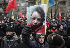 UKRAINE-JOURNALIST/ A protester holds a picture of journalist Tetyana Chornovil, who was beaten and left in a ditch just hours after publishing an article on the assets of top government officials, during a protest rally in front of the Ukrainian Ministry of Internal Affairs in Kiev December 25, 2013. Chornovil, a prominent activist who has given speeches at recent anti-government protests, told police her car was stopped by a vehicle just after midnight. A group of unidentified men got out…