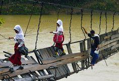 Pupils go to school crossing a damaged suspension bridge, in Lebak, Indonesia.