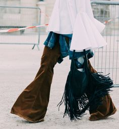 Nesta fotografia de streetstyle vemos que a influência hippie dos anos 70 voltou e não é de todo subtil, neste caso as calças à boca de sino em bombazine, o casaco de ganga, a túnica fluída e as franjas abundantes na carteira perfazem o estilo.