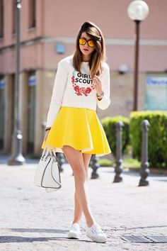 How to Style Your Sneakers in Summer - Bright yellow skater skirt, a preppy graphic sweatshirt, cool mirrored sunglasses, and classic white sneakers