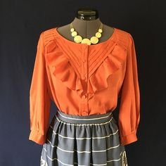 """HP Anthro """"Nicoleta Blouse"""" by Maeve Beautiful details!!  Tucks & Ruffles draw the eye to the yoke of Maeve's button-up. The color is a medium muted orange. 3/4 length sleeves with single button cuffs. Closes with a row of covered buttons down the front, & a scooped neckline. Unfitted, boxy, relaxed silhouette. Size 8. Bust measured flat across is 20 inches, back of neck to hem is 24.5 inches. In Perfect condition with No wear or tear. HP 12-26 Wardrobe Refresh Party! Anthropologie Tops…"""