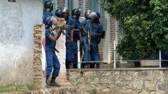 armed police in Burundi take shelter by a house in the capital Bujumbura