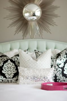 Beautiful master bedroom design with soft gray brown walls paint color, silver sunburst mirror, blue tufted headboard bed, white damask pillows, silver metallic lumbar pillow and hot pink round faux croc mirrored tray.