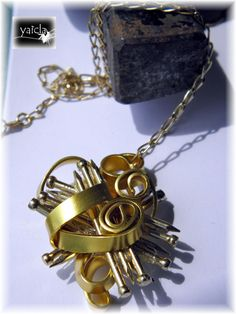 Colgante realizado con piezas de ferreteria,en este caso unas puntas doradas e hilo de aluminio dorado.