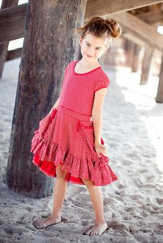 PAPER WINGS PUFF SLEEVE RED DRESS WITH GATHERED POCKETS    Can a dress be fancy and casual at the same time? This one can. The t-shirt cut on top in red with cream pinstriped material is made from organic cotton so it is soft on her skin. The extra touches like drawstring bows and gathered pockets, along with puffed sleeves and ruffles in red and cream spots dress it up.