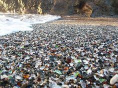 Glass Beach - Fort Bragg, California - Once used as a rubbish dump this place finally got a clean up in 1967 however the millions of tiny glass shards were too difficult to pick up and therefore left to the unrelenting ocean waves to deal with in their own way, turning the sand into a sparkling, multicolored bed of smooth glass stones now known as Glass Beach. The beach is now an unofficial tourist attraction incorporated into surrounding MacKerricher State Park.