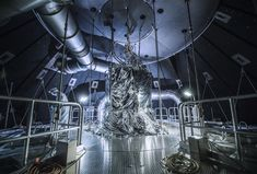 This legacy photo from May of 2015 shows the fifth floor of Chamber A at Johnson Space Center. Chamber A is the giant thermal vacuum test chamber that will be used for an end-to-end test of the James Webb Space Telescope in 2017.  This photo was taken before the start of a test on the Webb telescope Pathfinder. The Pathfinder is a test version of the telescope.   The contamination control engineer on the left is doing his final FOD (Foreign Object Debris) inspection. In the center of this…