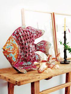 BUSCANDO A NEMO Un banco de peces, con un magnífico y llamativo ejemplar policromado a la cabeza, procedente de Becara, compone un simpático bodegón sobre la consola de madera sin tratar, de Mestre Paco.