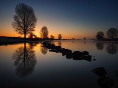 Just before sunrise the river Maas was still and looked like mirror. I loved the light and the reflections!