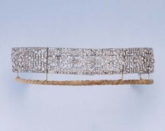 AN ART DECO DIAMOND BANDEAU TIARA  Designed as an openwork diamond band, the articulated panels centring on six daisy motifs, with tiara frame and brooch fitting, convertible into a choker, a longer and shorter bracelet, and a brooch, circa 1920, choker 32.8 cm long, bracelets 17.5 and 15.2 cm long, brooch 3.6 cm across, in original Carrington & Co Ltd red leather fitted case.