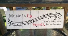 Rustic sign Music is Life. . .Thats why our Hearts have beats is painted on a white background with black lettering and red lettering. It is approximately 24x8. Our signs are made from reclaimed pallet boards and are naturally distressed. This sign comes with a sawtooth picture hanger and is meant to be displayed indoors. Top coat and color options available.