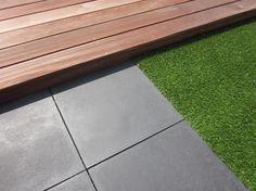 Mooie combinatie die in elke tuin toepasbaar is: hardhouten vlonder, terrastegels en kunstgras.