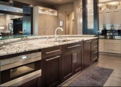 Custom dream kitchen with dark hardwood cabinets, granite counter tops and custom lighting by CHC Creative Remodeling