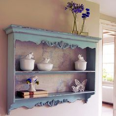 This fabulous carved wall rack is ideal for almost any wall in any room. Show off your essentials in the kitchen, display your bathroom beauty products in gorgeous jars on its shelves or adorn with photo frames and other keepsakes in your bedroom, lounge or hallway. Its delightful pale blue colouring, distressed exterior and unfinished background print add to its rustic and charming character. Definitely a G favourite.