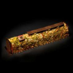 bûche de François Pralus   Chocolat Pralus de Madagascar à 75% de cacao et onctueuse mousse à la pistache, le tout enrobé de zestes d'oranges amères, d'éclats de pistache et d'amandes grillées.